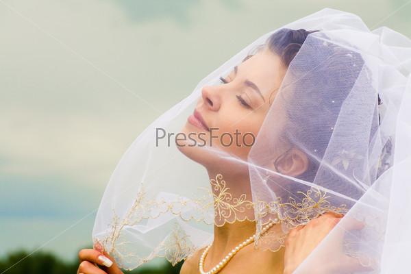 Восхитительная и счастливая невеста на фоне неба