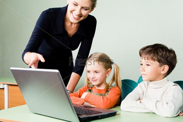 Современная учительница объясняет задание своим ученикам глядя в ноутбук