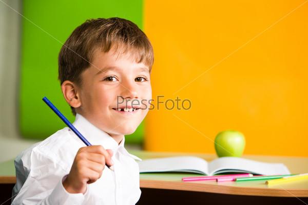 Радостный ученик сидит за партой перед раскрытой тетрадью