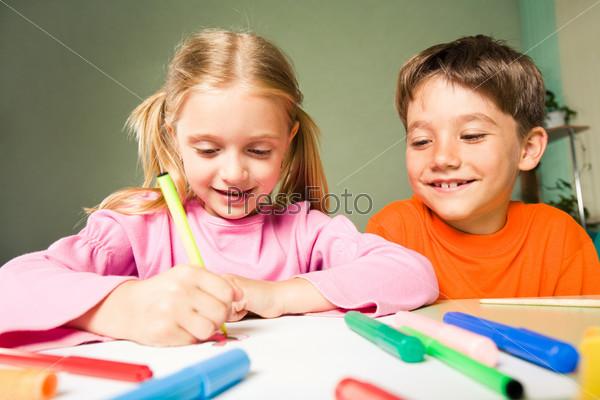 Старший брат наблюдает за тем, как рисует его сестра сидящая за столом