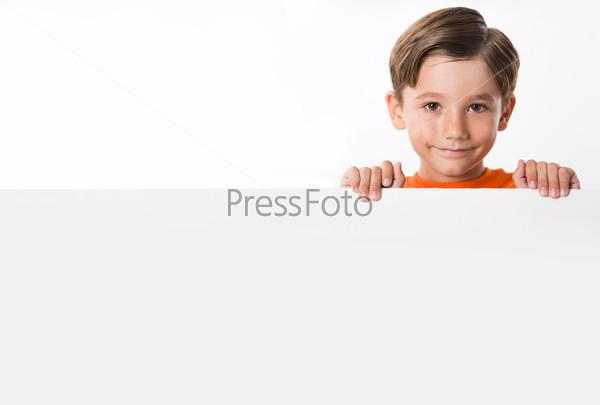Хорошенький мальчик держит белый плакат перед собой