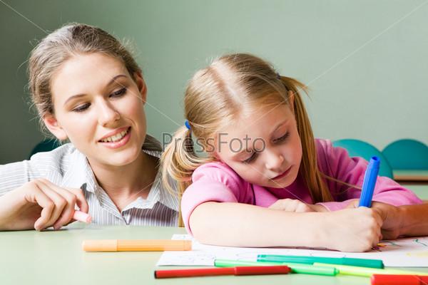 Заботливая мама наблюдает за своей дочкой, котоая рисует за столом