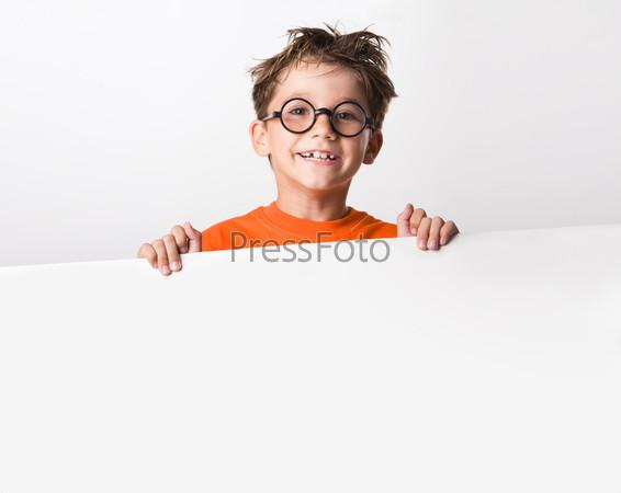Довольный взлохмаченный ученик в очках держит белый плакат и смеется
