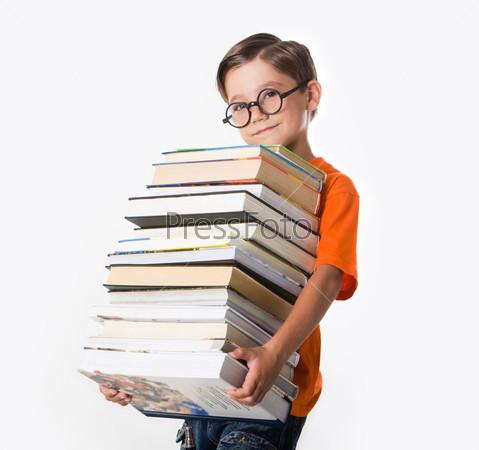 Очаровательный мальчик в круглых очках стоит с грудой книг и улыбается