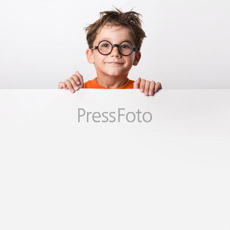 Умный подросток в очках стоит за белой поверхностью и улыбается