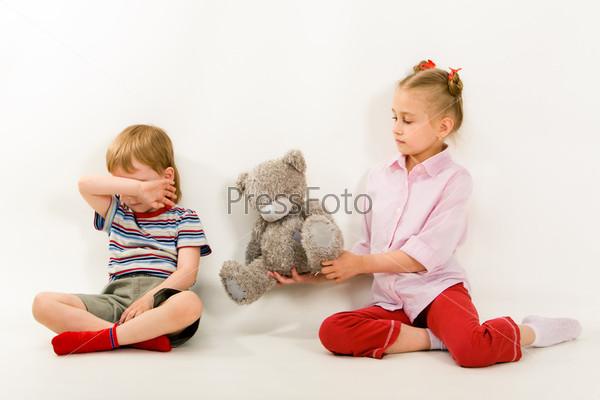 Девочка протягивает обиженному брату плюшевого медвежонка