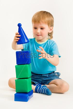 Фотография на тему Мальчик строит пирамидку сидя на полу