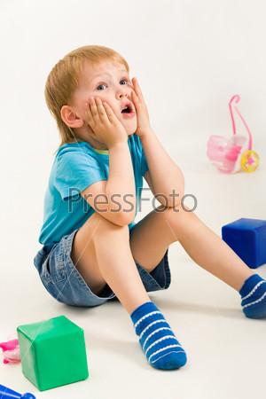 Удивленный малыш сидит на полу в окружении игрушек