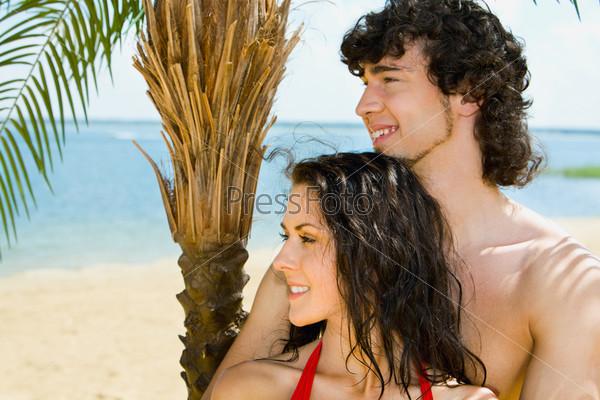 Счастливый молодой человек обнимает девушку на пляже
