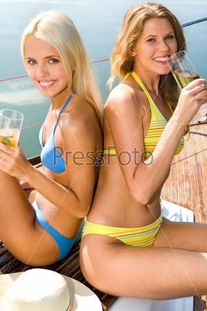 Две очаровательные девушки в купальниках пьют коктели