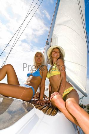 Фотография на тему Две очаровательные девушки отдыхают на яхте во время круиза