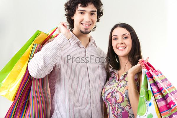 Молодая пара держит в руках пакеты с покупками