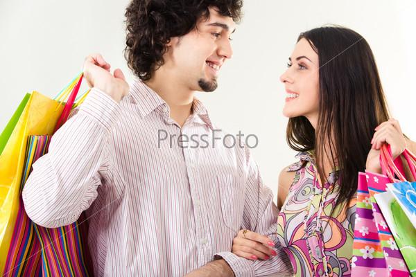 Счастливая пара с сумками для покупок стоит на белом фоне и смотрит друг на друга