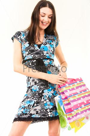 Девушка улыбается и смотрит на цветные пакеты в ее руках