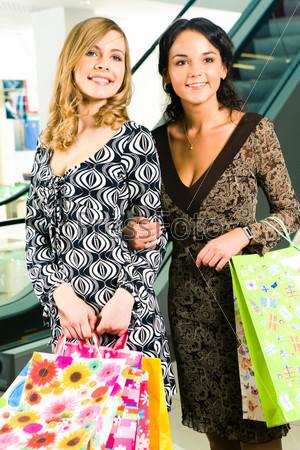 Счастливые девушки с пакетами в руках стоят в торговом центре