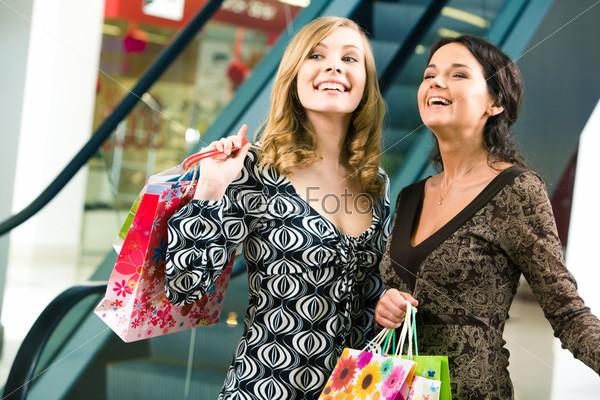 Две счастливые девушки смотрят на что-то в магазине и смеются