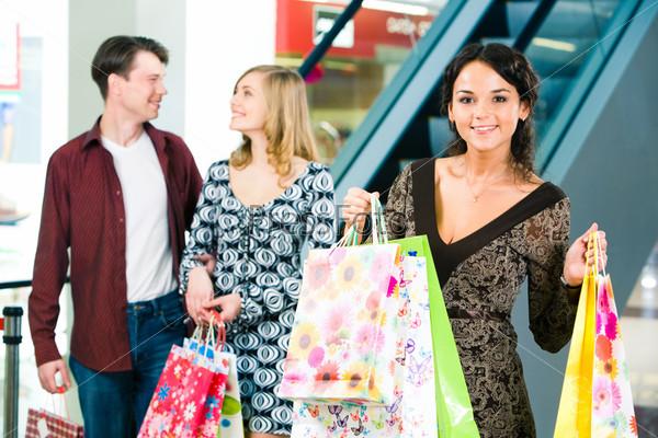 Счастливая девушка держит в руках пакеты с покупками  и смотрит в камеру на фоне молодой пары