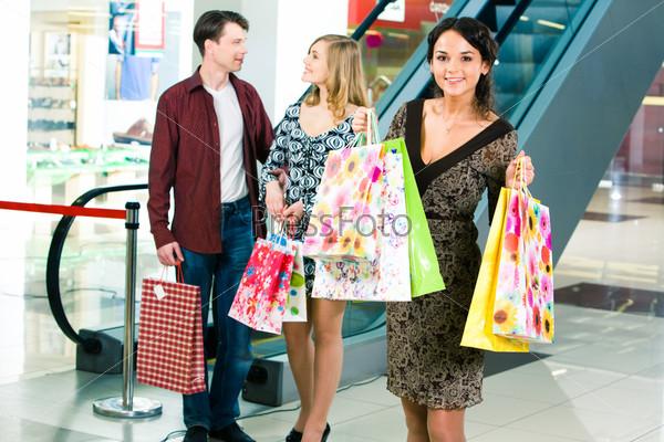 Девушка стоит в торговом центре с пакетами покупок на фоне молодой пары