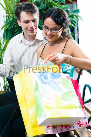 Девушка с молодым человеком сидят в торговом центре и смотрят, что у них лежит в пакетах