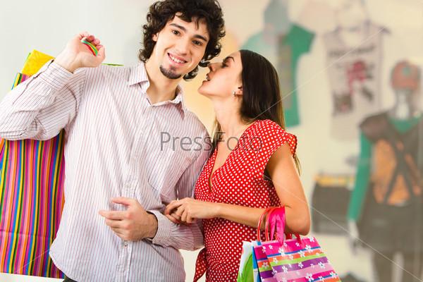 Девушка шепчет что-то молодому человеку в торговом центре