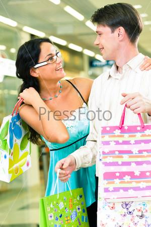 Молодая пара с пакетами в руках идет по торговому центру и мило беседует