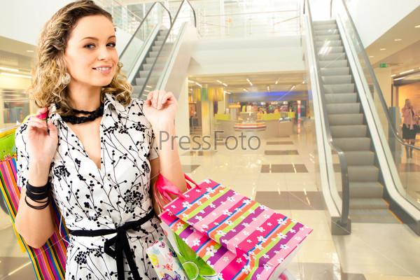 Счастливая блондинка стоит с покупками в торговом центре