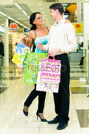 Милая пара стоит в магазине с разноцветными пакетами