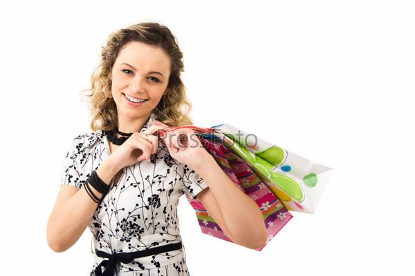 Очаровательная девушка держит бумажные пакеты на белом фоне