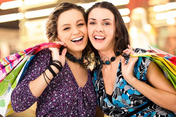Веселые девушки смеются в торговом центре