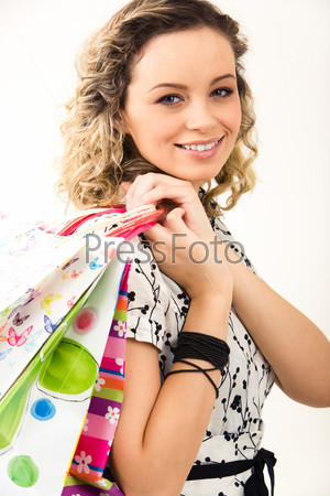 Девушка улыбается и держит разноцветные пакеты на белом фоне