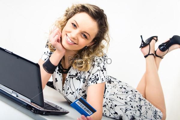 Девушка лежит перед ноутбуком и держит в руке кредитную карточку