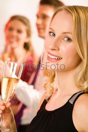 Привлекательная девушка держит в руке бокал шампанского на фоне молодой пары