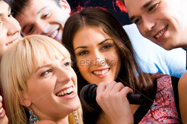 Девушка поет с друзьями в караоке