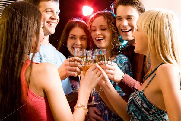 Друзья держат в руках бокалы шампанского и чокаются