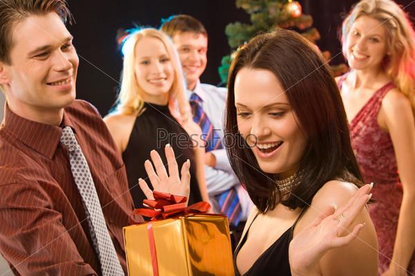 Мужчина дарит очаровательной девушке подарок на Рождество