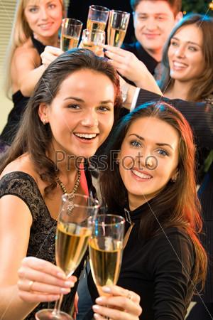 Две девушки улыбаются и поднимают бокалы шампанского на фоне своих друзей