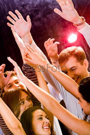Группа молодых людей танцует в ночном клубе
