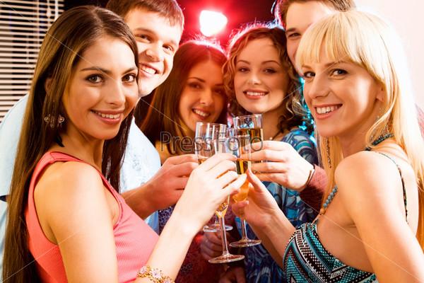 Молодые люди улыбаются и пьют коктели