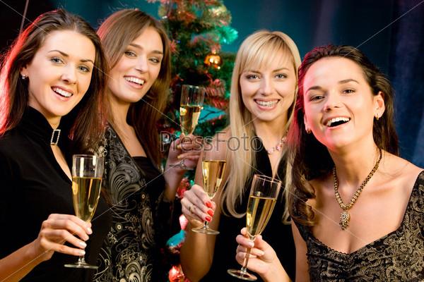 Четыде девушки с бокалами шампанского на фоне новогодней елки