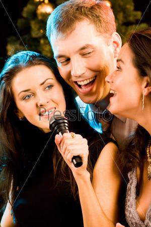 Молодые люди поют в микрофон