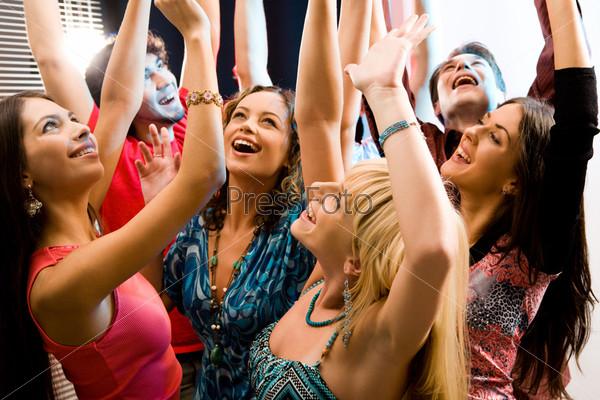 Молодые люди смеются и поднимают вверх руки
