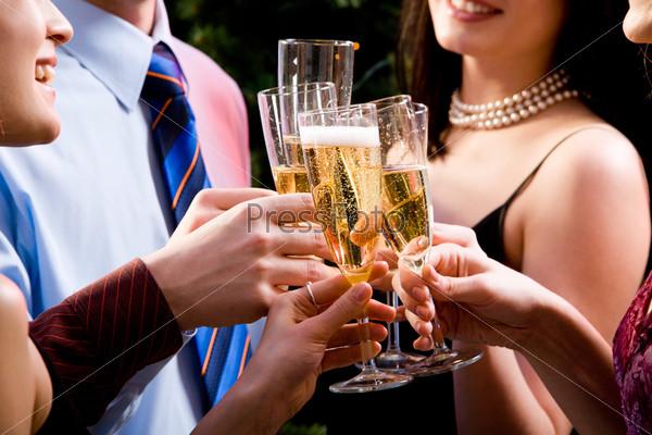 Руки молодых людей держат бокалы с шампанским во время тоста