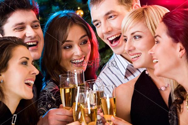 Счастливые друзья с бокалами в руках на вечеринке