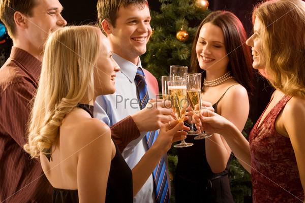 Друзья на вечеринке поднимают бокалы с шампанским и произносят тост