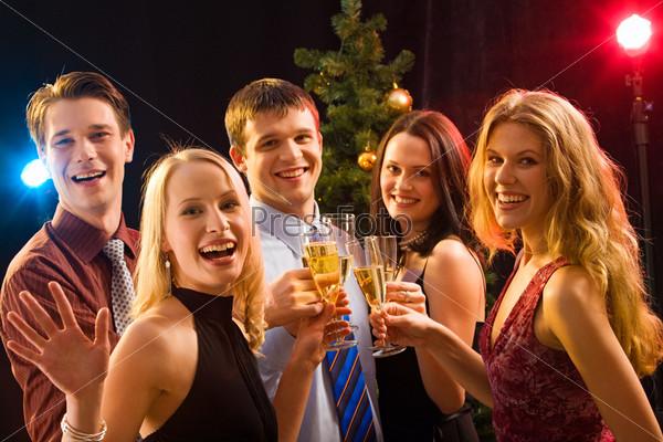 Фотография на тему Молодые люди с бокалами на рождественской вечеринке