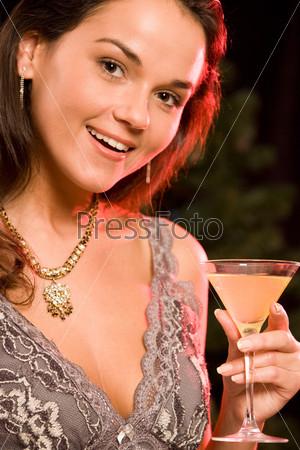 Восхитительная девушка держит в руках бокал шапманского