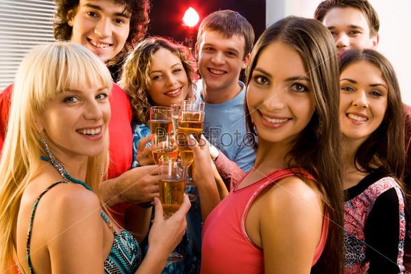 Друзья держат в руках бокалы с шампанским и улыбаются