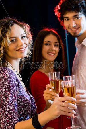 Молодые люди с бокалами шампанского в руках смотрят в камеру