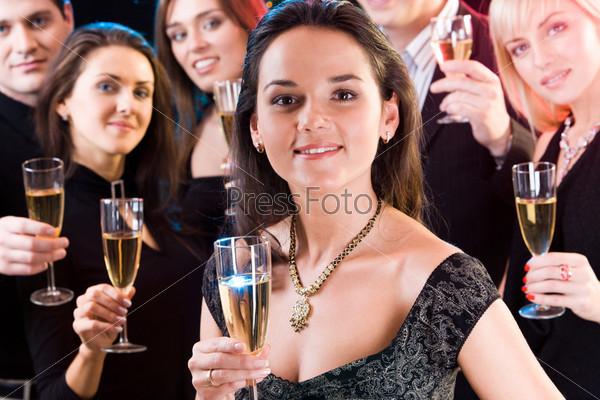 Прекрасная девушка держит бокал на фоне своих друзей