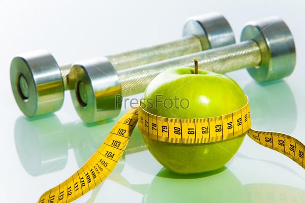 Зеленое яблоко обвитое лентой и две гантели